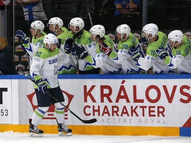 Slovinský hokejista Anže Kuralt přijímá gratulace od spoluhráčů.