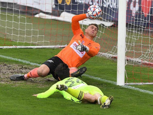 Christián Herc z Karviné sleduje míč před brankářem Pardubic Jiřím Letáčkem v utkání 30. kola Fortuna ligy.