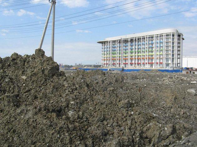 Za haldami hlíny vzniká hotel pro olympijskou rodinu.