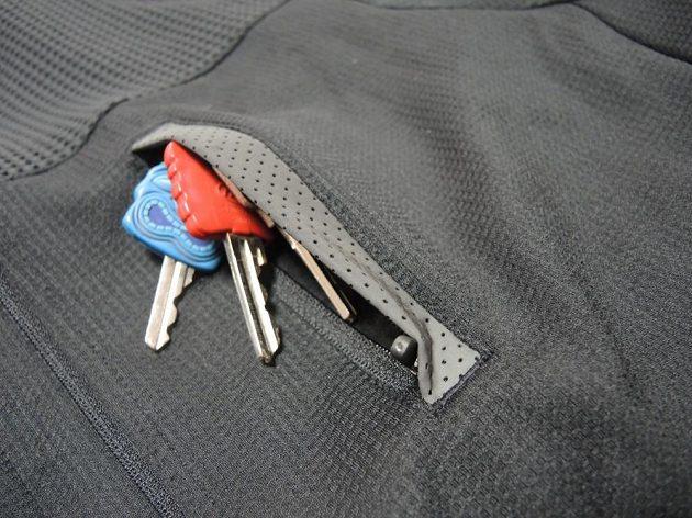 Detail hrudní kapsy s reflexním lemem.