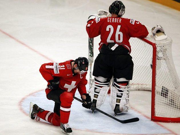 Zklamaní hokejisté Švýcarska po inkasovaném gólu z hole Hjalmarssona. Vlevo obránce Mathias Seger, vpravo brankář Martin Gerber.