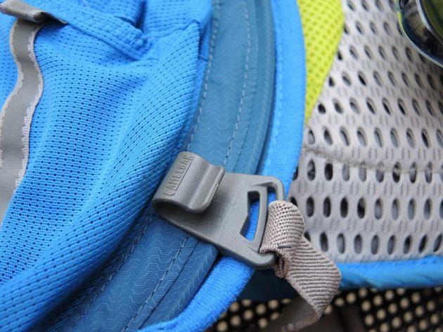 Běžecký batoh/běžecká vesta CamelBak Ultra 10 - posuvná přezka hrudního pásku slouží zároveň jako držák hadice.