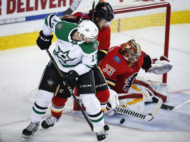 Český útočník Dallasu Stars Radek Faksa zkouší překonat svého krajana v brance Calgary Davida Ritticha.