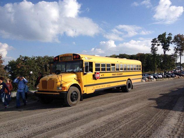 Školní autobusy, které vozí diváky k hlavnímu vstupu.