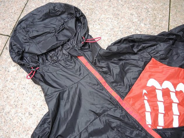 CompresSport Trail Hurricane Jacket - jedním z nejnápadnějších prvků větrovky je excentrický zip.