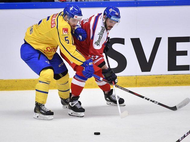 Švédský hokejista Mikael Wikstrand v souboji s Martinem Frkem na Švédských hokejových hrách.