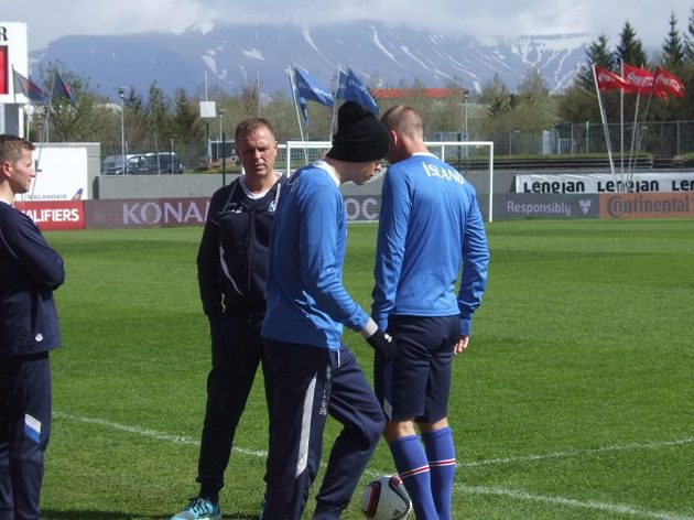 Červen na Islandu - zasněžené kopce za stadiónem, vlajky ve větru a kulich s rukavicemi pro méně otužilé hráče...