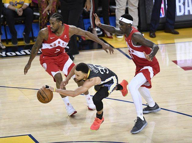Hvězda Golden State Stephen Curry se probíjí mezi dvojici Raptorů Pascalem Siakamem (vpravo) a Kawhim Leonardem.