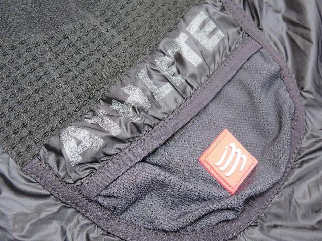 CompresSport Trail Hurricane Jacket - malá kapsa na zádech má reflexní potisk a nášivku.