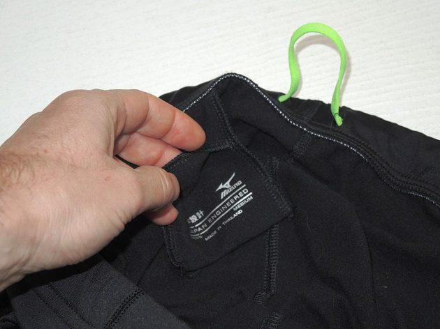Běžecké legíny Mizuno Breath Thermo Tights: Detail malé kapsičky a šňůrky sešité do kruhu.