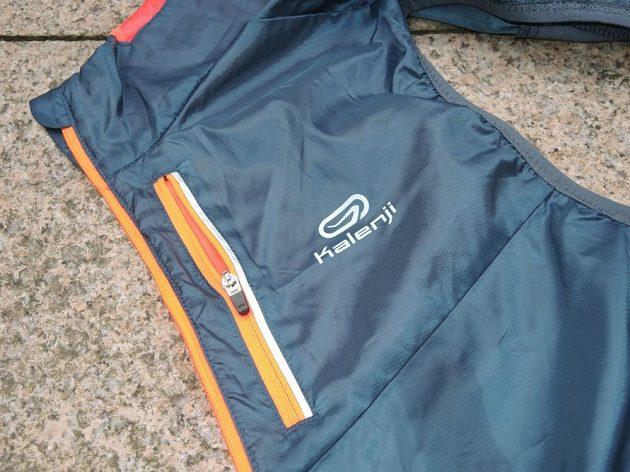 Trailová běžecká vesta Kalenji: Hrudní kapsa nese reflexní prvek.