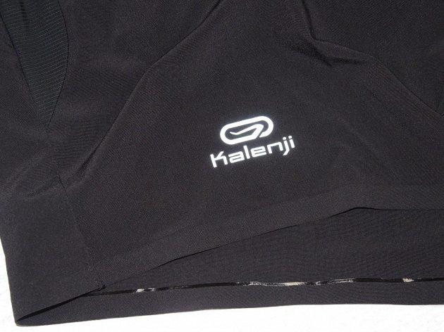 Trailové šortky Kalenji: Detail reflexního loga a svařovaných švů.