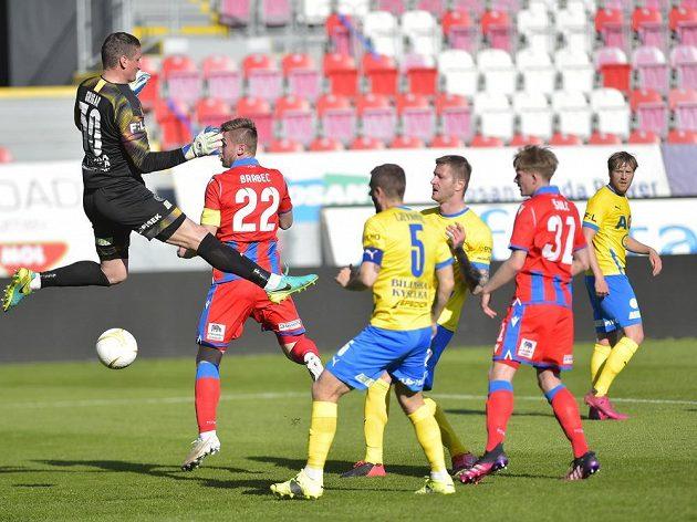 Brankář TeplicTomáš Grigar zasahuje před plzeňským Jakubem Brabcem v pohárovém semifinále.