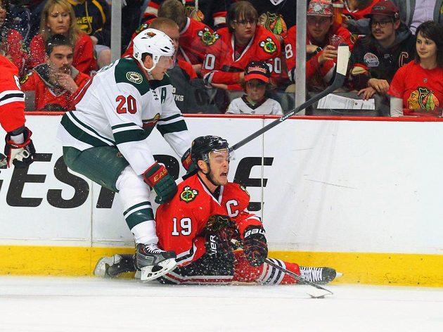 Kapitán Blackhawks Jonathan Toews (dole) se ocitl v nepříjemné pozici po souboji s Ryanem Suterem z týmu Minnesoty.