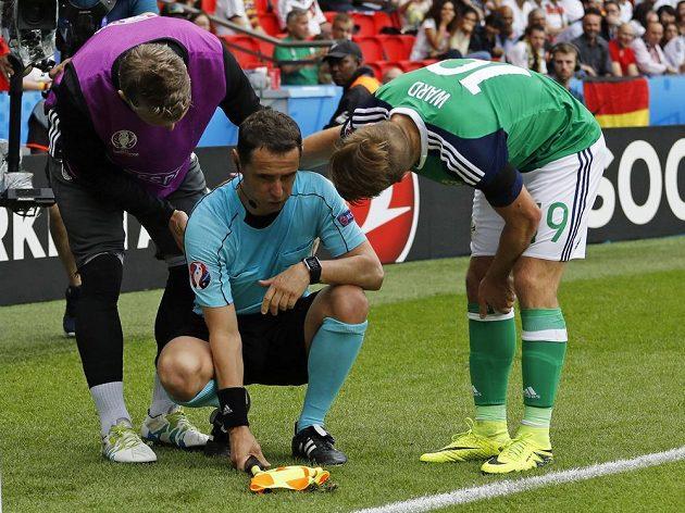 Severoirský fotbalista Jamie Ward a Němec Bastian Schweinsteiger se sklání nad asistentem rozhodčího, jehož zasáhl míč.