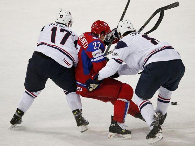 Američané Aaron Palushaj (vlevo) a Jacob Trouba zpracovávají ruského útočníka Alexeje Těreščenka.
