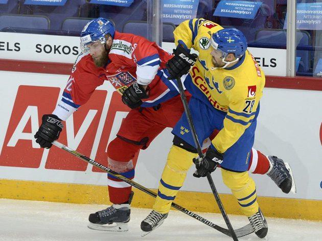 Český obránce Adam Polášek (vlevo) a švédský útočník Dick Axelsson bojují o puk v utkání Karjala.