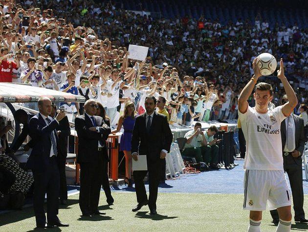 Gareth Bale pózuje před zaplněným stadiónem Santiaga Bernabéua.