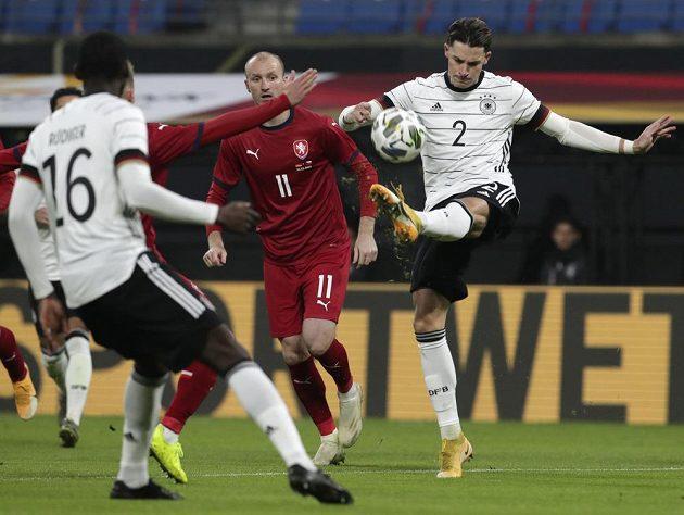 Němec Robin Koch se pokouší střílet, za ním český útočník Michael Krmenčík (11).
