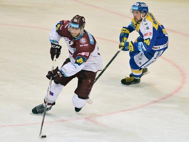 Sparťanský obránce Juraj Mikuš (vlevo) a zlínský forvard Roberts Bukarts v dohrávce 15. kola hokejové Tipsport extraligy.