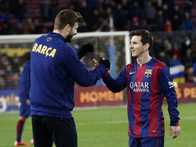 Lionel Messi z Barcelony a jeho spoluhráč Gerard Piqué (vlevo) po vítězném zápase s Levante.