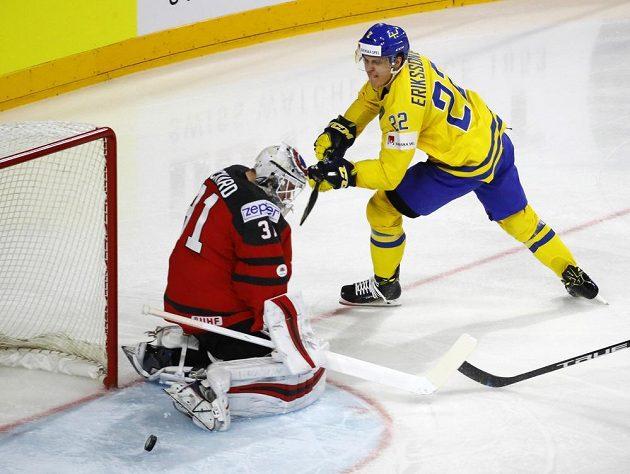 Joel Eriksson ze Švédska (ve žlutém) se snaží překonat kanadského brankáře Calvina Pickarda.