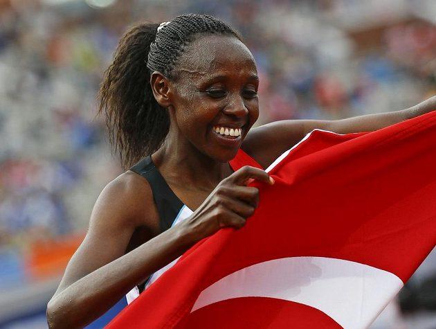 Běžkyně Yasemin Canová slaví vítězství v závodě na 10 000 metrů s tureckou vlajkou.