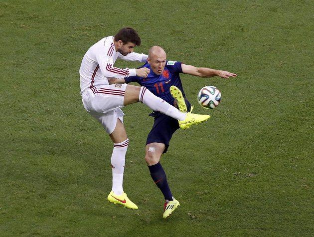Španělský stoper Gerard Piqué (vlevo) v souboji s Nizozemcem Arjenem Robbenem.