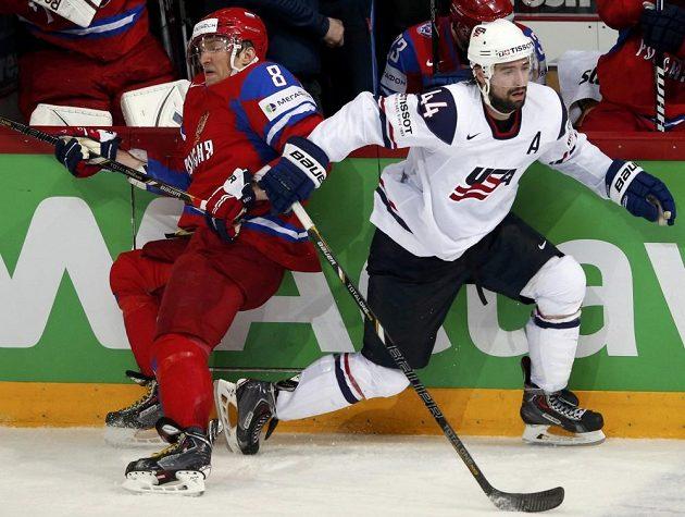 Ruský snajpr Alexandr Ovečkin (vlevo) v souboji u hrazení s Natem Thompsonem z USA.