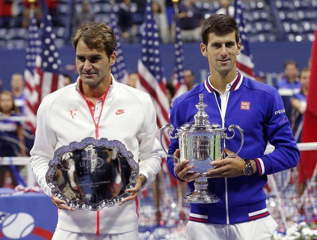 Roger Federer (vlevo) pózuje s trofejí pro poraženého finalistu US Open vedle vítězného Novaka Djokoviče.