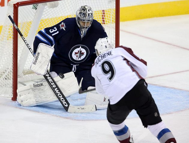 Útočník Colorada Matt Duchene se snaží překonat brankáře Winnipegu Ondřeje Pavelce.