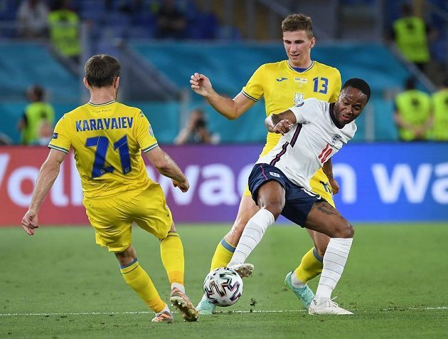 Anglický fotbaista Raheem Sterling v akci během čtvrtfinále EURO s Ukrajinou. Atakuje jej Ilja Zabarnyj.