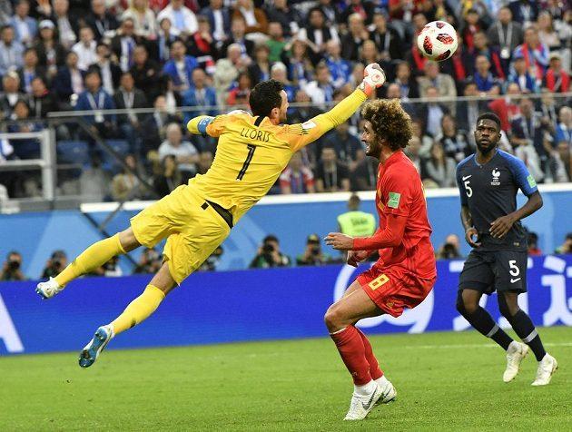 Francouzský brankář Hugo Lloris sbírá míč z hlavy Marouana Fellainiho z Belgie.