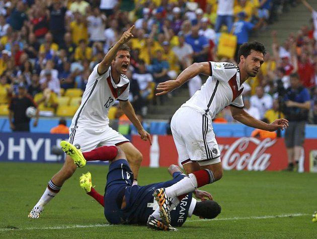 Němec Mats Hummels (vpravo) sleduje míč mířící po jeho hlavičce do sítě. Thomas Müller už jásá, Francouz Raphael Varane (na zemi) je bezmocný.