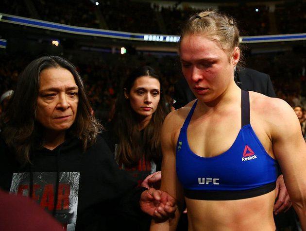 Vyzývatelka Ronda Rouseyová opouští bojiště v doprovodu své matky.