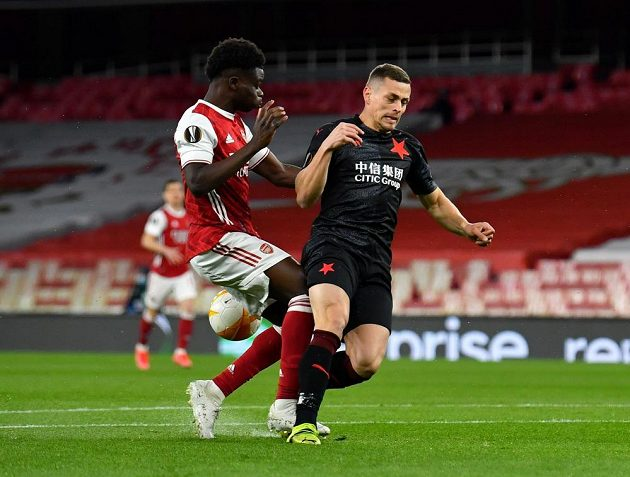Bukayo Saka bojuje o míč s Tomášem Holešem