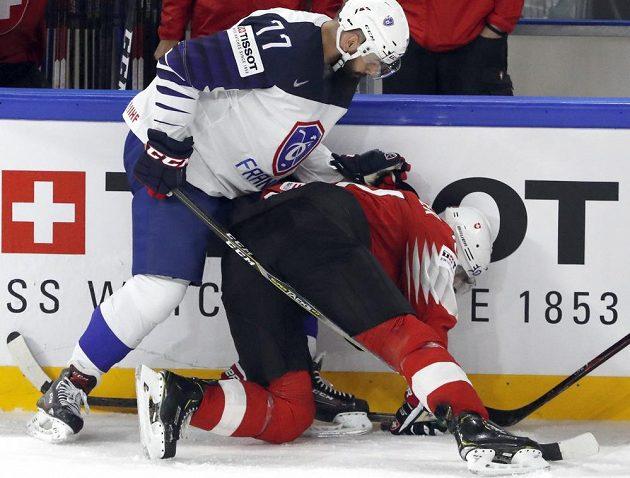 Francouzský hokejista Sacha Treille v souboji se Švýcarem Ninem Niederreiterem v utkání mistrovství světa.