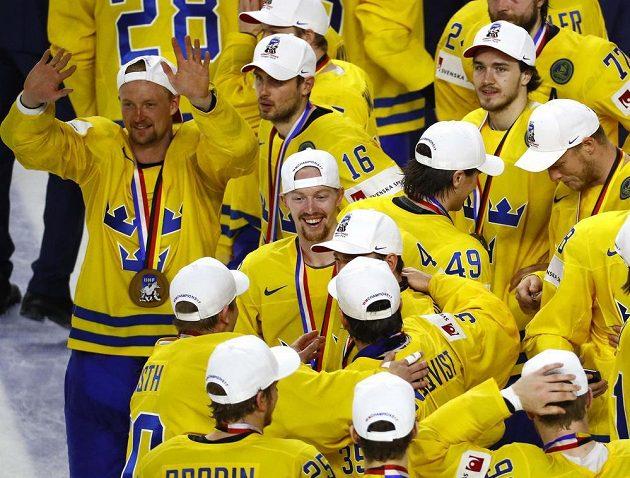 Zlaté medaile na hrudích švédských hokejistů.