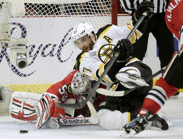 Útočník Patrice Bergeron z Bostonu padá před brankou Coreyho Crawforda z Chicaga v úvodním finále Stanley Cupu.