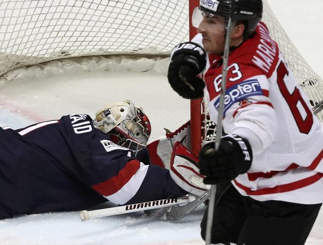 Kanaďan Brad Marchand slaví, americký brankář Keith Kinkaid po inkasovaném gólu bezmocně leží na ledě.