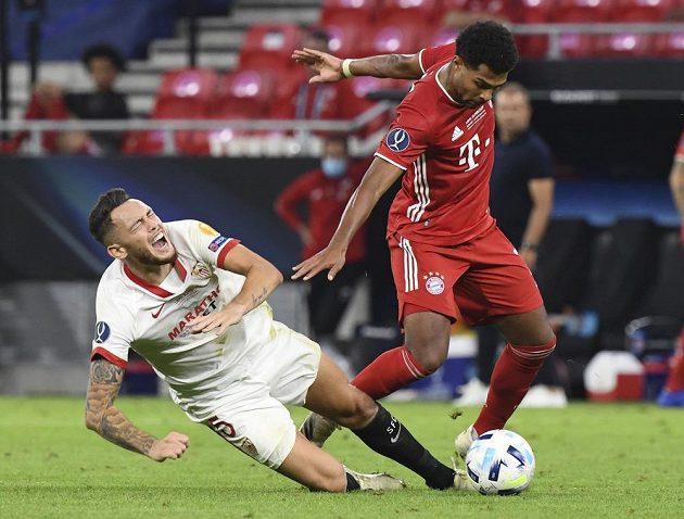 Lucas Ocampos ze Sevilly padá po střetu s Benjaminem Pavardem z Bayernu.