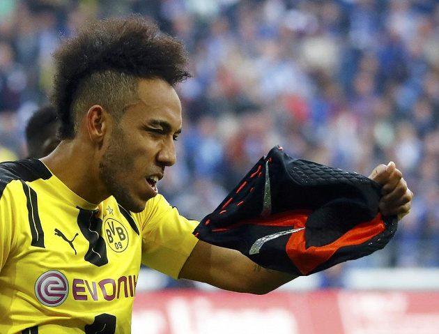 Dortmundský střelec Pierre-Emerick Aubameyang se chystá nasadit masku poté, co vstřelil gól do sítě Schalke.