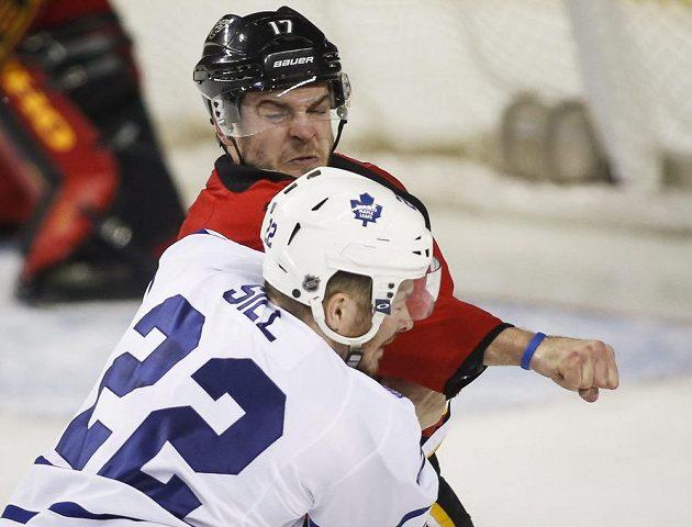Torontský Zach Sill (22) schytává úder od Lance Boumy. (AP Photo/The Canadian Press, Jeff McIntosh)