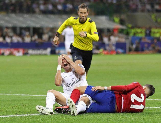 Zadák Bílého baletu Pepe (v bílém) po střetu s Yannickem Ferreirou Carrascem z Atlétika Madrid.