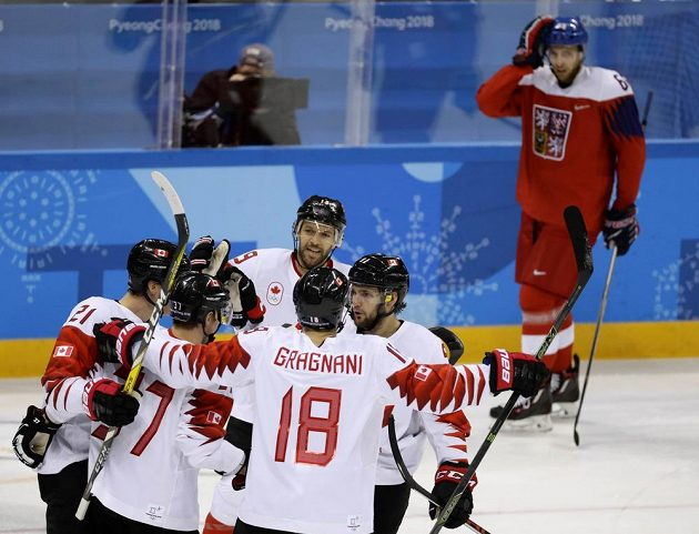 Kanadští hokejisté oslavují branku v české síti.