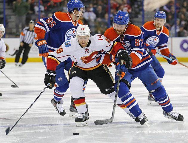 David Musil (87) ve svém prvním utkání v NHL krotí průnik Matta Stajana (18).