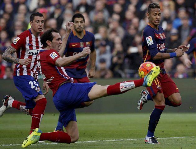 Obránce Atlétika Madrid Diego Godín odkopává míč před brazilským útočníkem Neymarem z Barcelony.