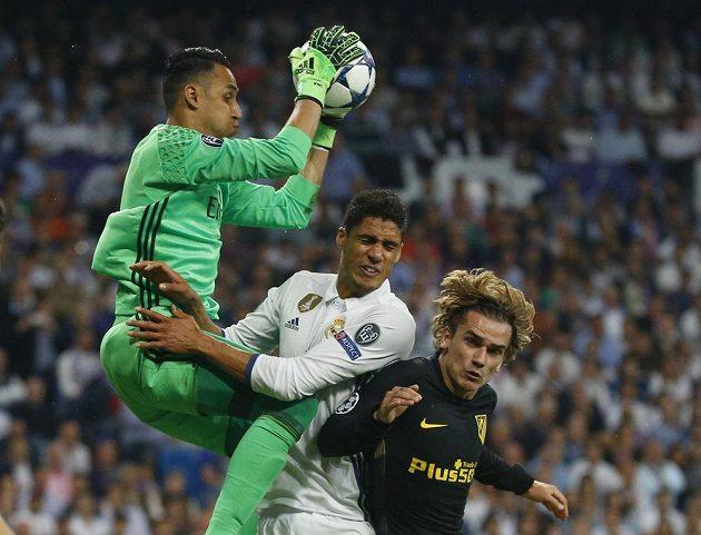 Brankář Realu Madrid Keylor Navas krotí míč v rukavicích za pomoci obránce Raphaela Varaneho. Hvězdný útočník Atlétika Antoine Griezmann se z zakončení nedostal.