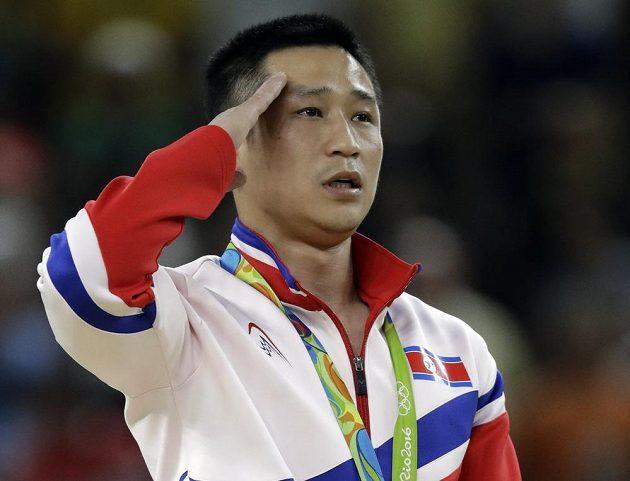Severokorejec Ri Se Kwang, vítěz přeskoku, salutuje během státní hymny.
