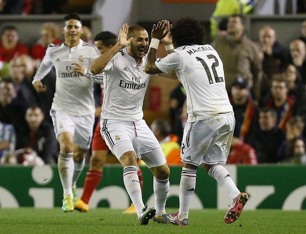 Fotbalisté Realu Madrid Karim Benzema (vlevo) a Marcelo (v pozadí James Rodrigues), slaví gól proti Liverpoolu v Lize mistrů.